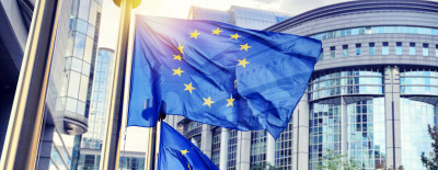 EU flags waving in front of European Parliament building.